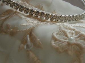 detail krajky na šatech a čelenka