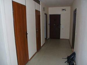 pohľad od obývačky na vchodové dvere, po ľavej strane kúpelka, wc, šatník, napravo dvere do spálne (pôvodný stav)