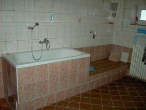 Spodní prádelna, vyvýšená vana, vedle sokl na kterém bude stát pračka a sušička.