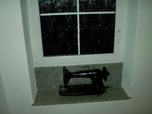 Zbytek šicího stroje zdobí okno na schodišti. Spodní část slouží jako stojan pod akváriem.