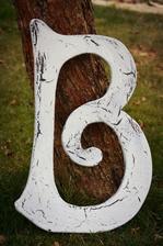 Počáteční písmeno ze jména nevěsty. Dřevotříska s trhaným nátěrem.