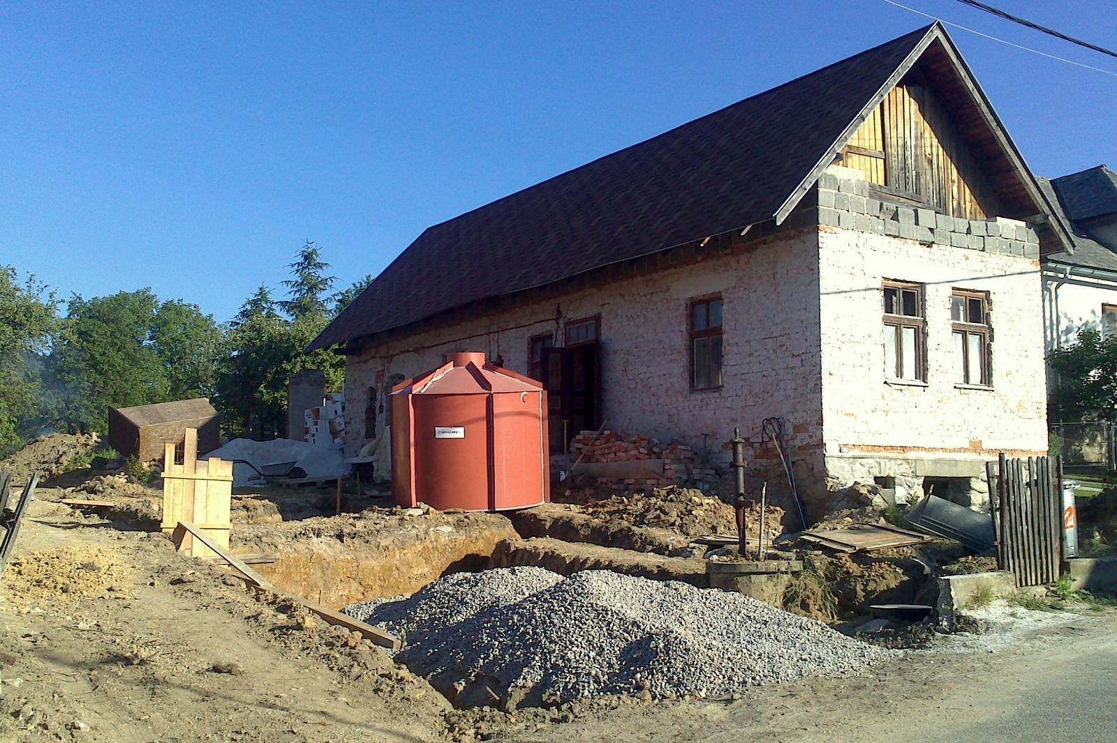 Rekonštrukcia domčeka z roku 1937 - Jún 2014 - odkopanie miesta pre budúce státie. Vzadu plastová žumpa s objemom 9 m3, ktorá bude zakopaná nad budúcim múrom.