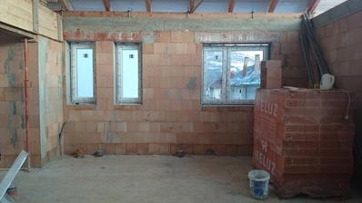 """Pohľad do budúcej kuchyne, druhého WC (úzke okno vľavo) a kúpeľne (úzke okno vpravo). Tam, kde sú tehly, určené na vymurovanie """"jadra"""",  bude neskôr varná doska"""
