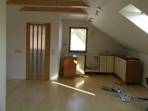 a část nové kuchyně a dveře do koupelny