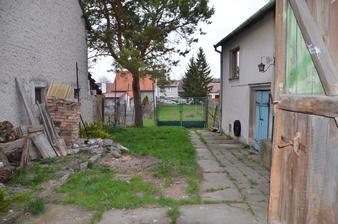 """vzadu za vraty zahrada, napravo modré dveře do vinného sklepa, nad ním """"společenská místnost"""""""