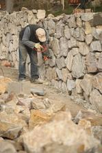 Vysekáva sa nadbytok betónu. Kamene sa chystajú na špárovanie.