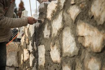 Kamenár so špachtličkou zoškrabne nechcený betón.