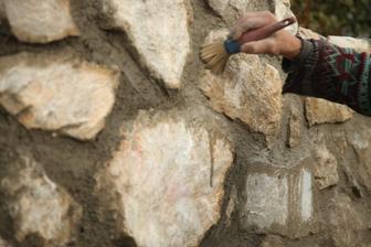 Druhý mokrým štetcom prečistí špáry a umýva kamene.