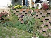 Oporný múrik z prefabrikovaných kvetináčov. Marianka 2005. Vystuženie zásypu umožňuje ukladať kvetináče vo väčšom sklone.