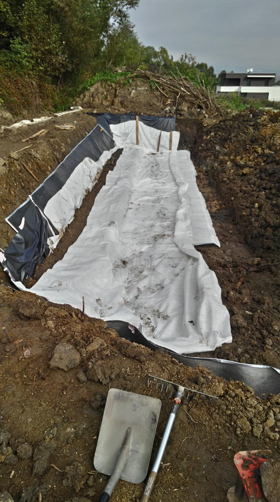 16. Problematický pozemok ( doplnené 21.8.2020 ) - 2019 10 Zľava : Na vrchole valu 1. tesniaca fóliu s geotextíliou. O svah opretá drenážno-tesniaci geokompozit. Rozprestretá geotextília pod budúcim vankúšom zo štrkodrvy s naväzujúcim vodorovným geokompozitom.