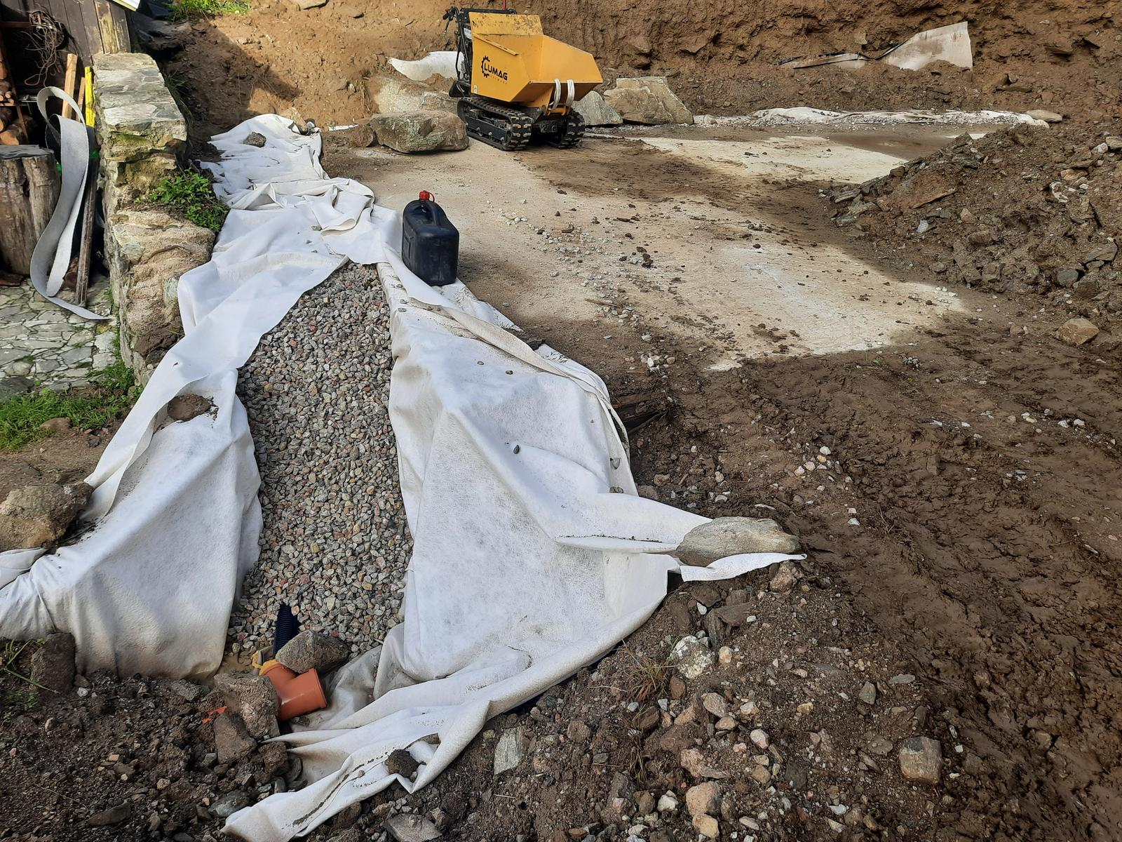 18. Stabilizácia výkopu pre stavbu a spevnenie + rozšírenie príjazdovej cesty. - 03. Drenáž zaústená do kanalizačnej rúry s prípravou na zaústenie druhej vetvy.