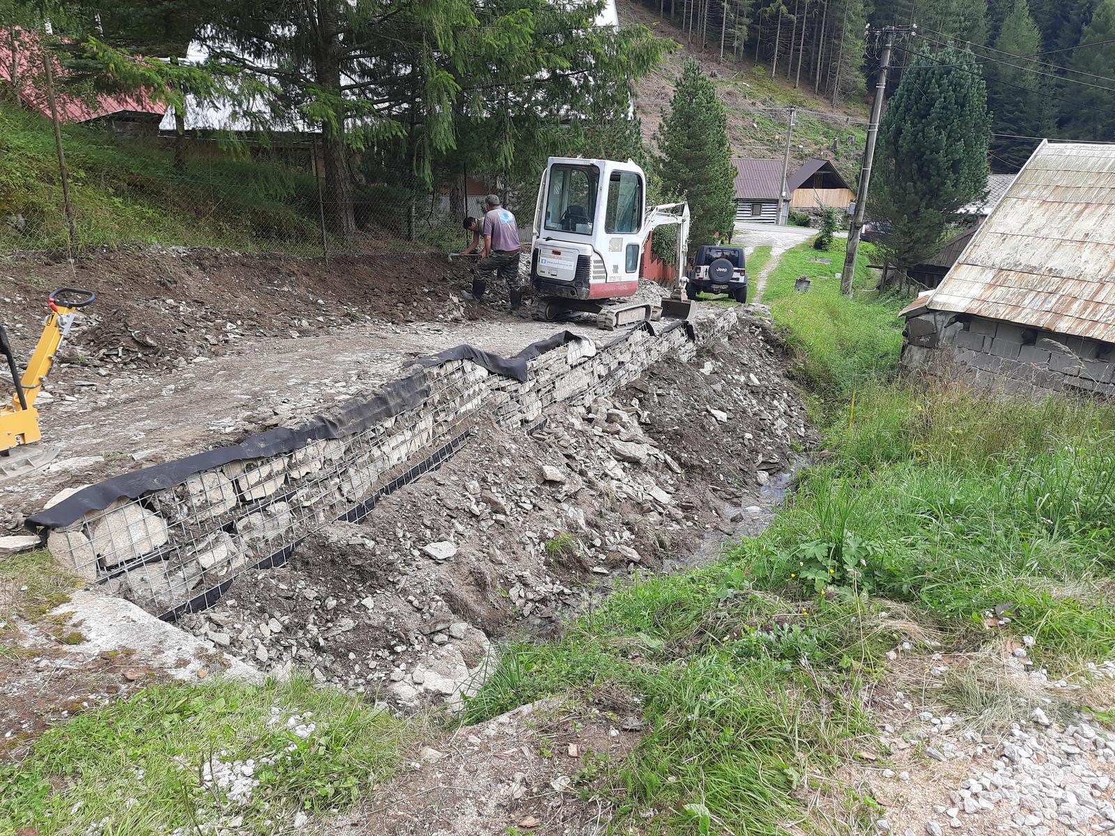 """18. Stabilizácia výkopu pre stavbu a spevnenie + rozšírenie príjazdovej cesty. - 06. Panely StoneSteel sú v čele vyplnené kameňmi z výkopu a """"kotvené"""" do svahu v dostatočnej dĺžke geomrežami. Proti vyplavovaniu je za kameňmi v čele netkaná geotextília."""