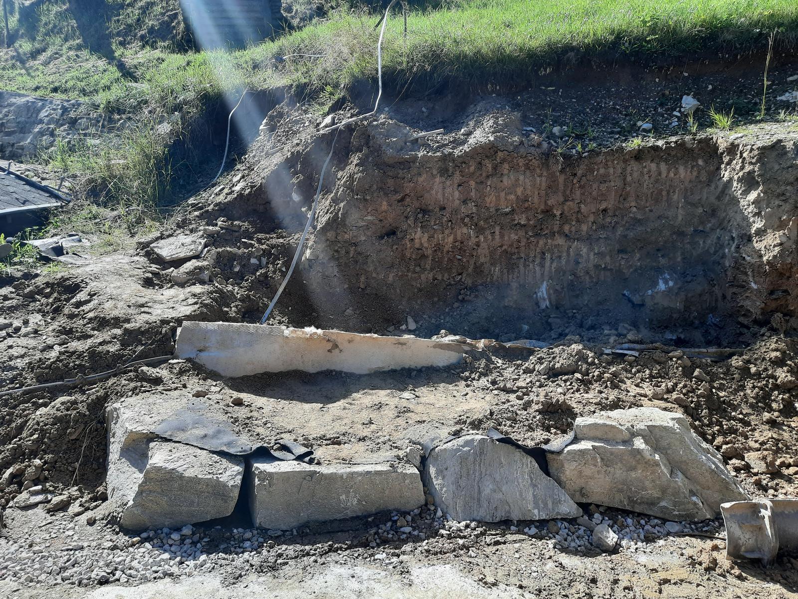 18. Stabilizácia výkopu pre stavbu a spevnenie + rozšírenie príjazdovej cesty. - 09. Založenie 1. vrstvy oporného múru. Vzadu trčí vodorovná drenáž pripravená na pojenie zvislej drenážno-tesniacehoi geokompizity za zásypom, ktorý odvedie všetky zvodnelé vrstvy do hĺbkovej drenáže.
