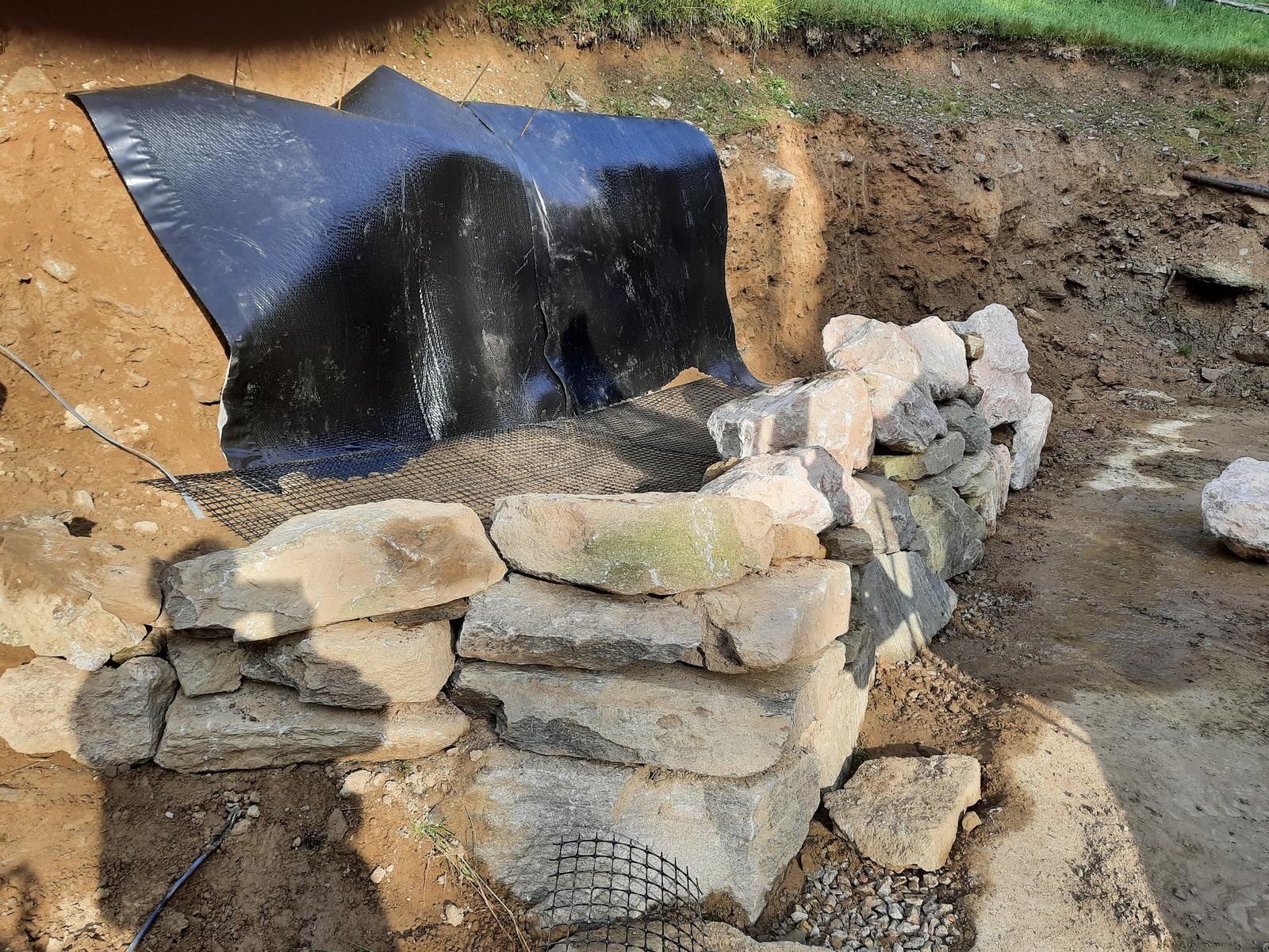 18. Stabilizácia výkopu pre stavbu a spevnenie + rozšírenie príjazdovej cesty. - 10. Drenážno- tesniaci geokompozit za zásypom bráni pranmienkom vody zo svahu preniknúť do zásypu.