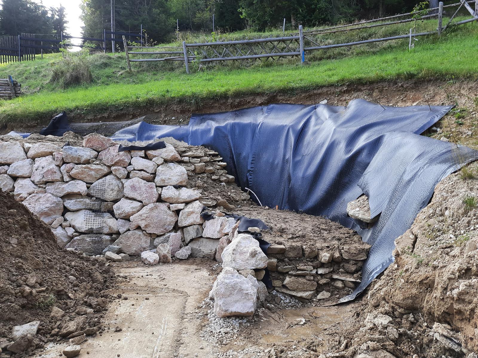 18. Stabilizácia výkopu pre stavbu a spevnenie + rozšírenie príjazdovej cesty. - 13. Na druhý deň bolo možné založiť kút oprného múru. Voda zo základovej dosky vsiakla ihneď do drénov.