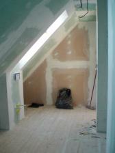 A pohled od vany zpet ke dverim, po leve strane dve stresni okna a priprava na zavesne WC. Na ruzove stene bude cerna komoda.
