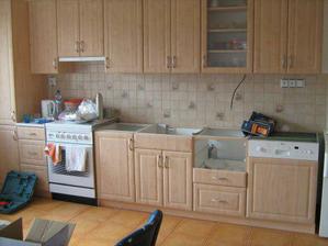 Kuchyn bez pracovni desky, do ktere se prave dává dřez..