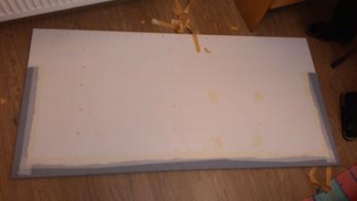 Zadná strana. Pri lepení poriadne ponaťahovať látku. Zafixované obyčajnou páskou. Čelo nie je nijako pripevnené na stenu, je len položené na zemi a pritlačené posteľou.