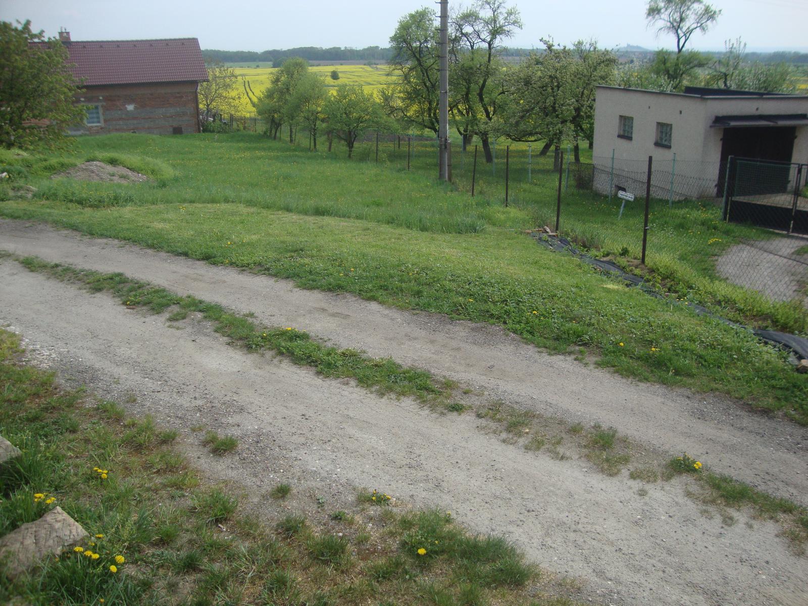 Venku (tam kde už to nevypadá jako staveniště) - naše zahrada (končí cca 4 m za tím betonovým sloupem, zatím vůbec nevím co si s ní počnu, je to hodně z kopce