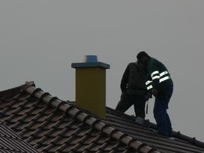 Šikovný chlapci naťahujú fasádu na komín.
