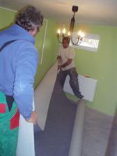 Táta s manželem pokládají koberec v pokoji pro hosty.