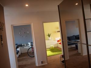Pohled z předsíně se zrcadlovou skříní do obou hlavních pokojů. V obýváku je trochu pracovního bordelu :) šicí stroje a opřené kolo.