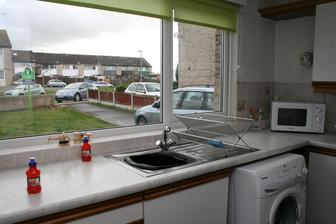 Pohled na predni zahradu a ulici. Cerny lavorek ve drezu, aby se usetrila voda. Britska specialita.