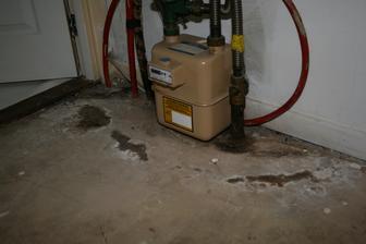 Prostor pod schody. Vlhkost prosakujici kolem dodatecne zabetonovane plynove a elektro pripojky. Zakryto kobercem, ktery za ta leta smrdel, ale vypadalo to normalne.