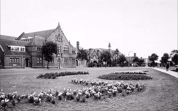 Budova skoly 1906 (s vezickou) a deti pred skolou. Sousedni budova vlevo v roku 1895. Foto cca 1960