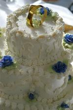 Naša torta... 3-poschodová ...bola celá biela ... s modrými ružičkami...na vrch sme chceli obrúčky...