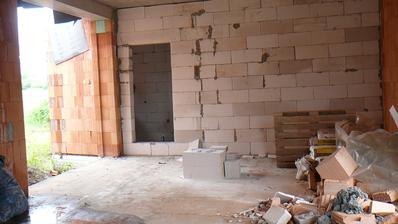 pohled z kuchyně přes obývací prostor na stěnu ložnice a dveře do šatny