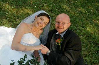 Šťastní novomanželé se válejí v trávě..