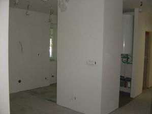 Chodba a kuchyňa v štádiu prerábky. Zrušili sme pôvodné dvere do kuchyne, zbúrali časť steny z chodby, zrušili izbu pre slúžku a zväčšili sme tak kuchyňu a vytvorili si kumbál, kde je za posuvnou zrkadlovou stenou schovaný aj elektrický bojler. Je to