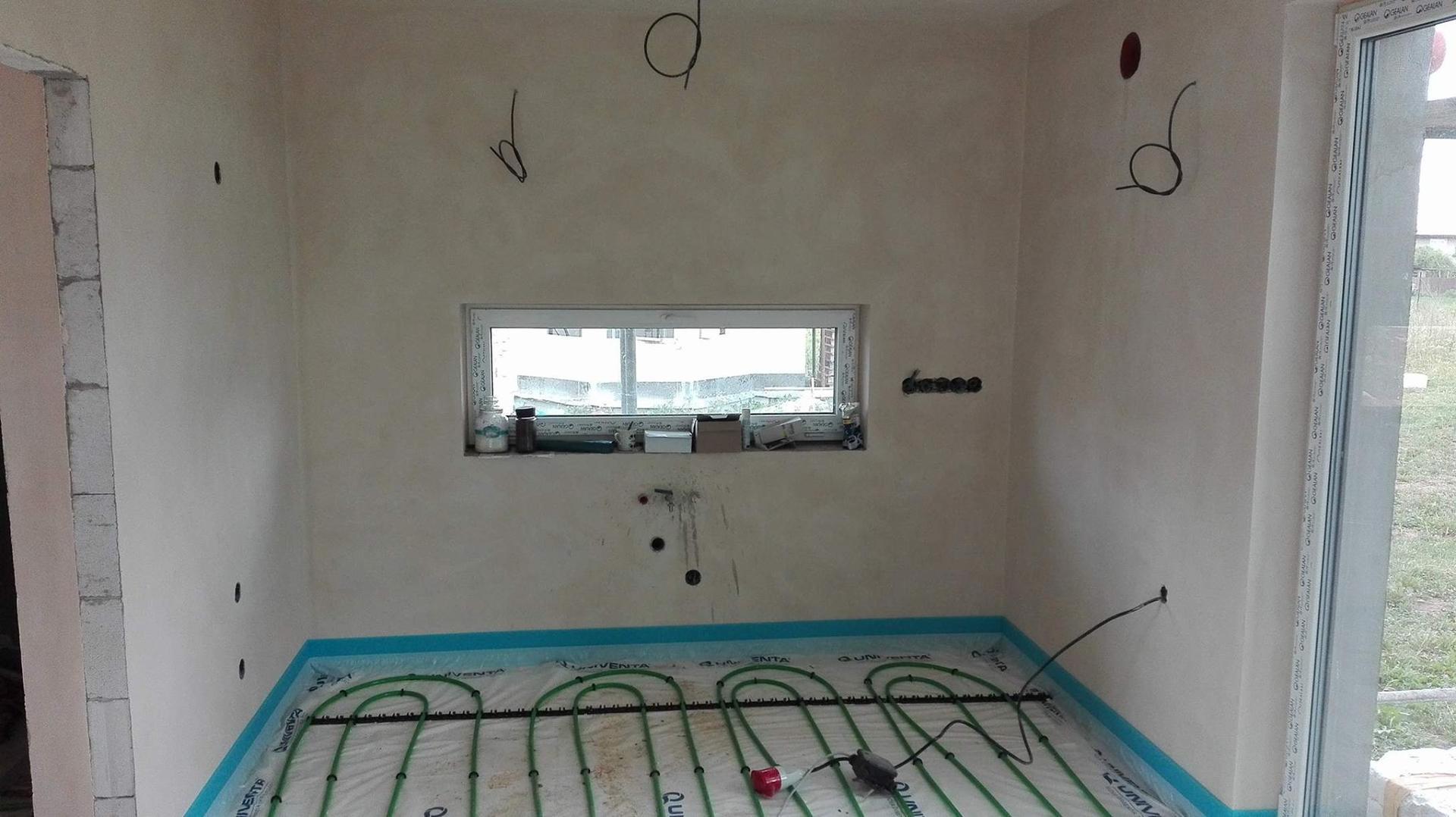 Stavba domu na kraji Prahy - Začínají intenzivní práce uvnitř domu. Pokládá se podlahové topení, aby nás v zimě nezábly nohy. Pohledové foto na kuchyňské okno.