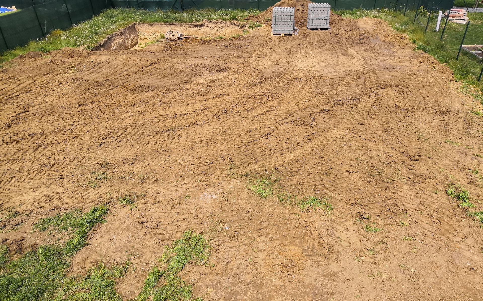 Zahrada na klíč - 13.5.2020 Profesionální úprava zahrady začala. Nejprve najel do zahrady bagr, který hrubě srovnal terén a připravil mírnou vlnu dolů uprostřed pozemku, kde bude mírný jednorázový svah. Zároveň již dorazilo ztracené bednění na stavbu jezírka.