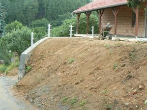 Srovnaný terén od silnice a sloupky nachystané na zábradlí (v této chvíli už ho máme, stejné jako u zadní zdi)