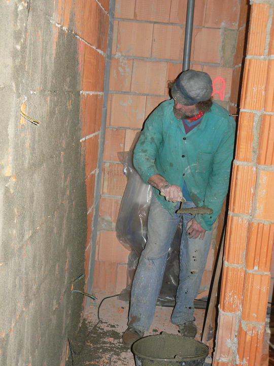 Táta špricuje zeď na záchodě, chystá pro zedníka, aby mohl rovnou naházet hrubou omítku
