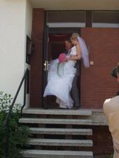 Novomanžel přenáší novomanželku přes práh nového společného hnízdečka