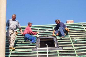 Pánové střechaři u jednoho z oken.