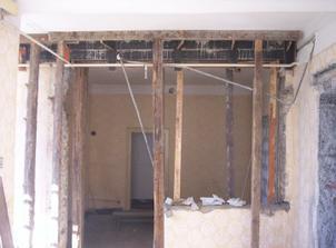 Okrem malého výklenku sa zbúrala celá stena medzi budúcou varnou a jedálenskou časťou kuchyne.  Vylievaný betónový preklad držia trámy.