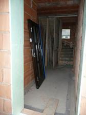 Nenasazené vchodové dveře a pohled na nové schodiště