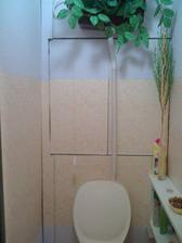 trochu upravené WC, zatím jen vinylová tapeta, poličky šikovně zakrývají trubky