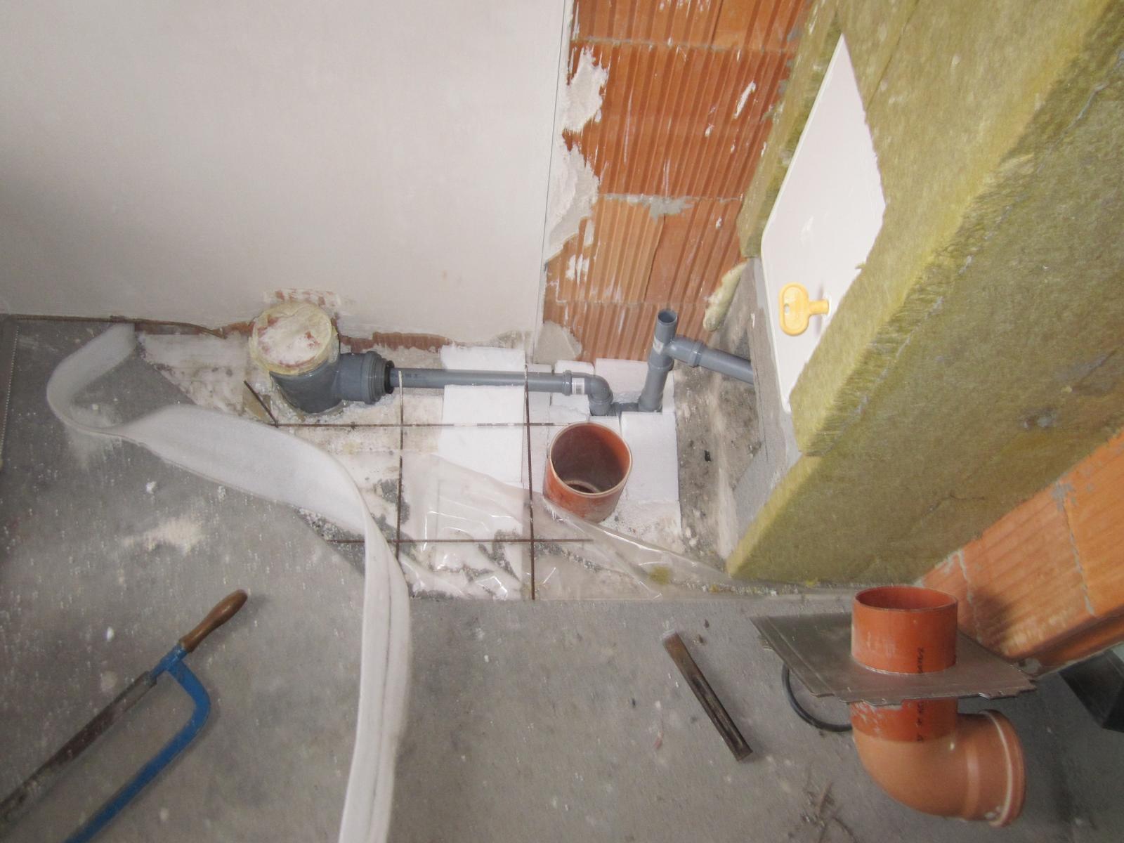 Odvetranie a odvodnenie komína SCH. UNI 20 - Sivé odpadové rúrky napojené na kanalizáciu - odvod kondenzátu. Z kolienok je vytvorený sifón, ktorý sa naplní vodou (alebo doplňuje po odparení) cez vrchný otvor (tam príde ešte štupeľ). Červená rúra v podlahe vyvedená na fasádu - odvetranie komína.