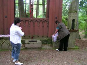 mamka instaluje dekoraci na kámen pod oltářem, Daniela provádí kontrolu