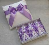 Bílý polštářek pod prstýnky s lila mašlí,