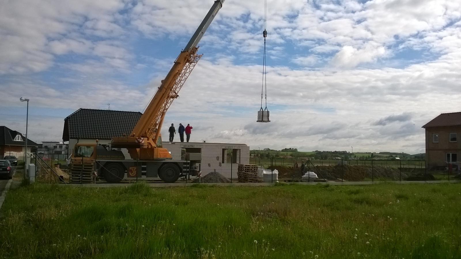 Stavba pasivního domu - Jeřáb vytahuje nahoru zdivo pro první patro.