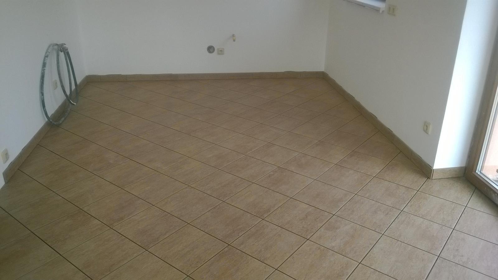 Stavba pasivního domu - dlažba v zatím osamělé kuchyni...