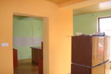 v pozadi zelienkava kuchyna, vpredu oranzova obyvacka