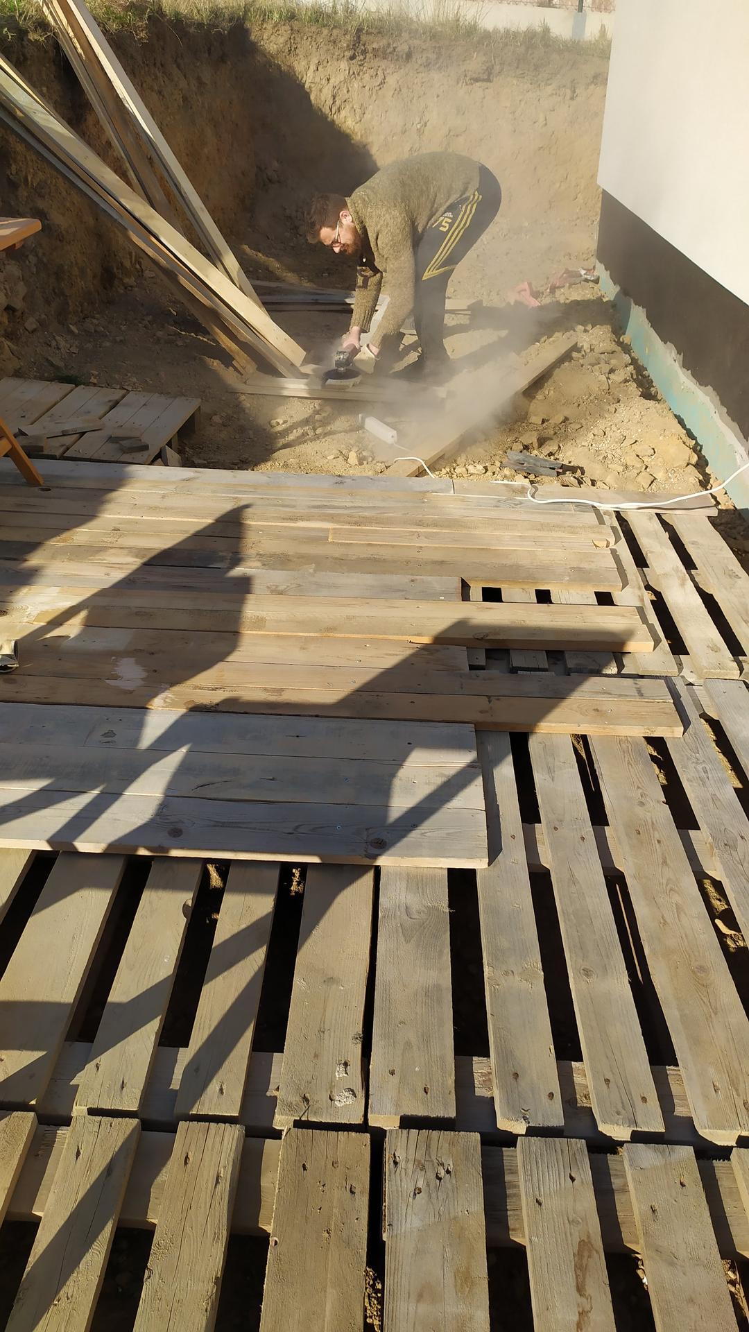 Náš domov ve svahu - Letos jsme se rozhodli udělat prozatimní terasy svépomocí - z palet a prken co nám a sousedům zbyly ze stavby
