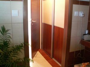 Pohľad do technickej miestnosti z kúpelne, za posuvnými dverami je práčka, bojler a kôš na bielizeň